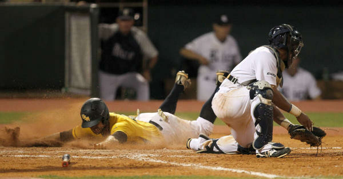 Southern Miss' Mark Ellis slides in for a run as Rice catcher Diego Seastrunk tries to block the plate in the seventh inning.