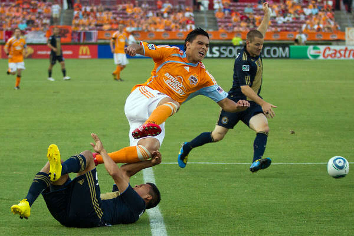 Dynamo forward Luis Angel Landin is upended by Philadelphia's Michael Orozco during the first half of Saturday's match at Roberston Stadium. Philadelphia rallied from a late deficit to win 3-2.