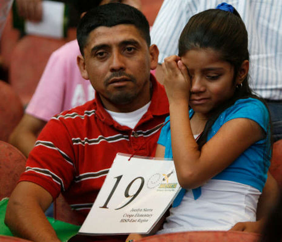 Jocelyn Sierra, of HISD's Crespo Elementary, cries as she is consoled by her father, Lazaro, after falling short in the bee. Photo: Julio Cortez, Chronicle