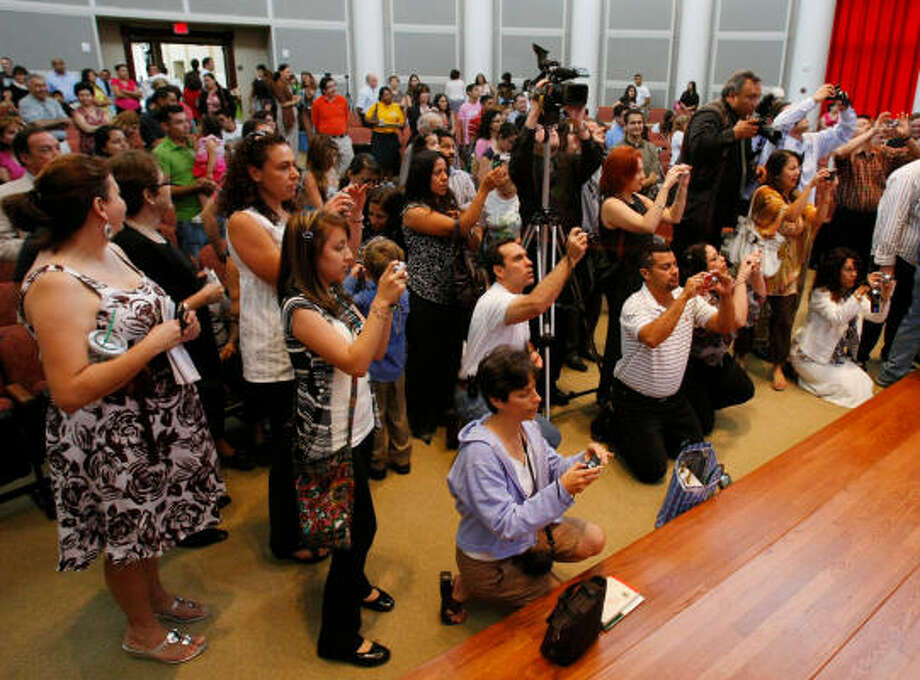 Proud parents try to take photos of their children. Photo: Julio Cortez, Chronicle