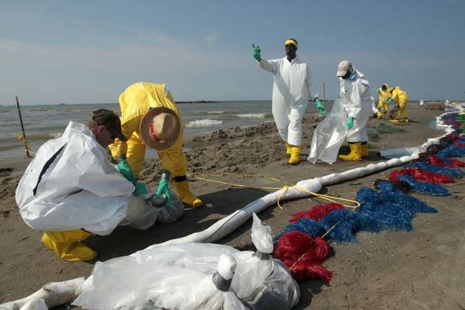 "Workers clean up oil residue along the beach in Port Fourchon, La. The risky ""top kill"" procedure to stop the oil spewing into the Gulf showed little success. Photo: Jae C. Hong, Associated Press"