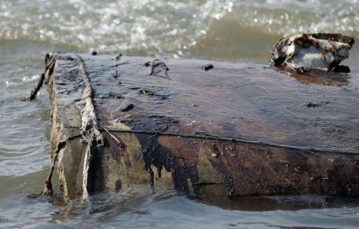 An oil-stained concrete sea barrier sits on the beach in Port Fourchon, La.