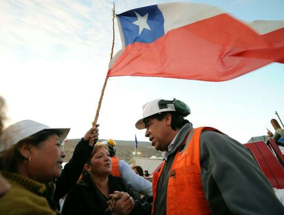 Relatives of the trapped miners greet a rescuer. On Tuesday, Chilean President Sebastian Pinera vowed not to abandon the workers in a telephone conversation with Luis Urzua, the shift foreman who has been the miners' leader. Photo: MARTIN BERNETTI, AFP/Getty Images