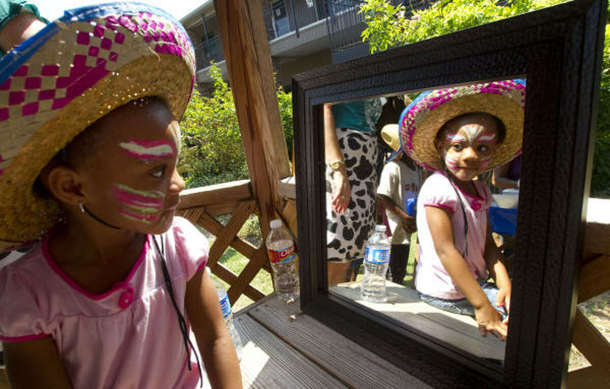 Celeste Thompson, 4, looks at her face paint in a mirror while celebrating the end of school.