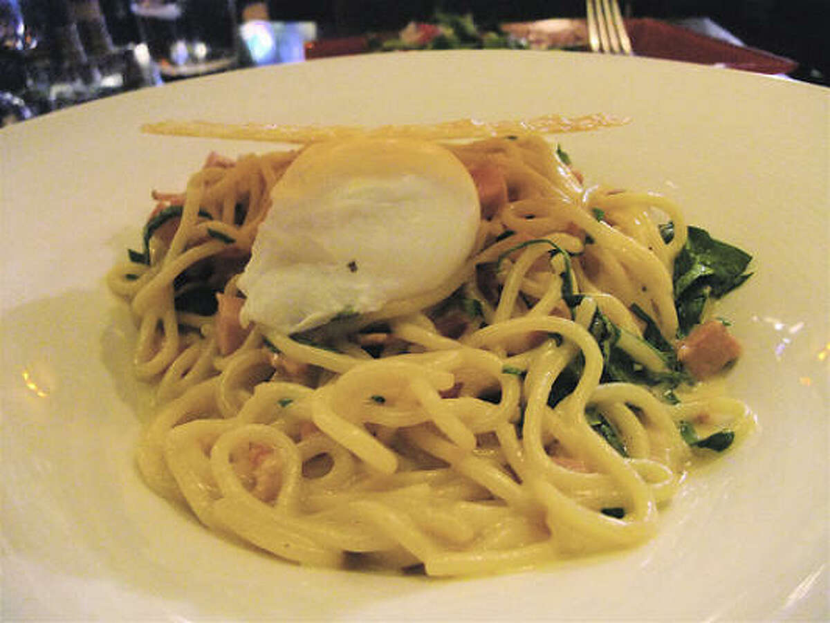 """The non-purist spaghetti """"carbonara"""" style with bacon, ham, a poached egg, spinach shreds and wearing a Parmesan frico hat atHubbell & Hudson Bistro."""