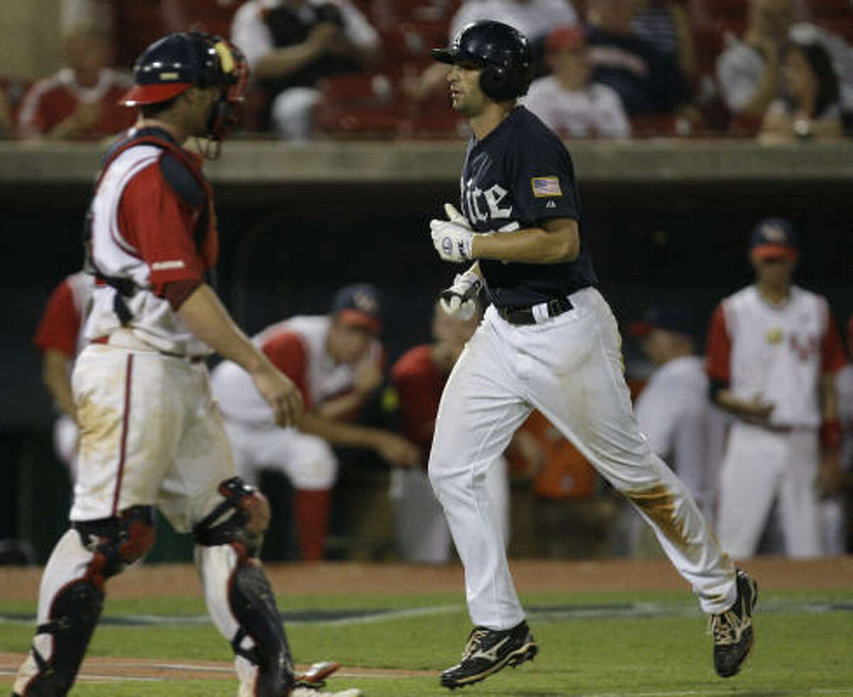 Houston catcher M. P. Cokinos, left, walks to the mound as Rice hitter Michael Funa, right, heads home on his home run during in the seventh inning.