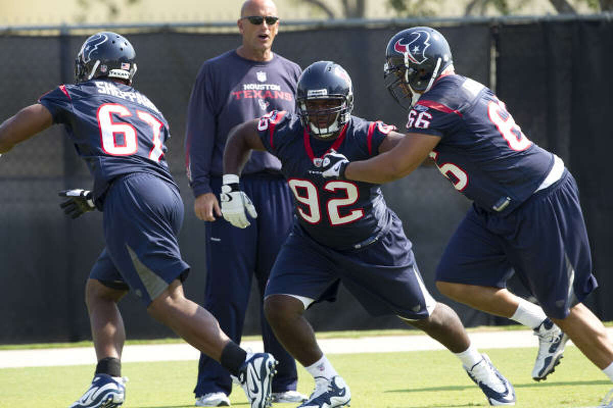 Texans defensive tackle Earl Mitchell, center, warms up with teammates Malcolm Sheppard, left, and DelJuan Robinson during a Texans' Organized Team Activities workout Thursday.