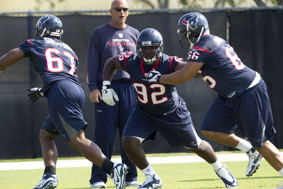 Texans defensive tackle Earl Mitchell, center, warms up with teammates Malcolm Sheppard, left, and DelJuan Robinson during a Texans' Organized Team Activities workout Thursday. Photo: Brett Coomer, Chronicle