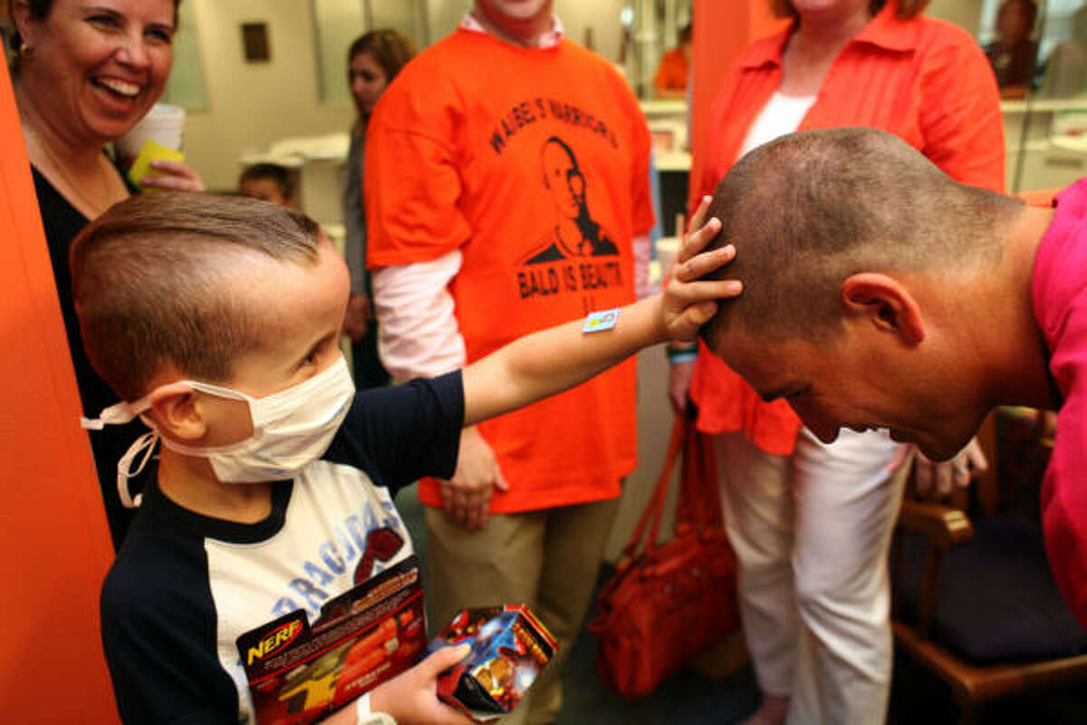 Peter Tsatsaronis, 7, touches the freshly shaved head of Bobby Boswell, of the Houston Dynamo soccer team.