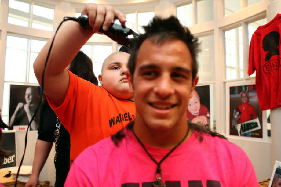 """Christina Huff, 8, of Mission, who is receiving cancer treatments at Texas Children's Hospital, shaves the head of Danny Cruz, of the Houston Dynamo soccer team.  This is the second year for the Bald is Beautiful campaign. Last year, """"Waibel's Warriors"""" raised over $40,000 with all proceeds benefiting Nick's Team and the Curing Childhood Cancer Fund charity supporting cancer research. The team will sport their new looks this Saturday when they play the Philadelphia Union. Photo: Johnny Hanson, Chronicle"""