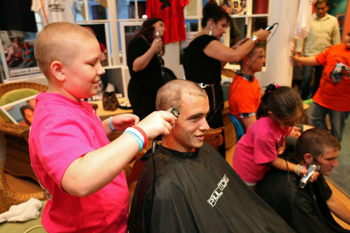 Caroline Fitzgerald, 11, of Houston, who is receiving treatment for Leukemia at Texas Children's Hospital, shaves the head of Cameron Weaver with the Houston Dynamo soccer team as he and his teammates had their heads shaved by cancer patients at the Texas Children's Cancer Center to benefit and raise awareness for the Dynamo's Craig Waibel's Warriors Bald is Beautiful fundraising event.