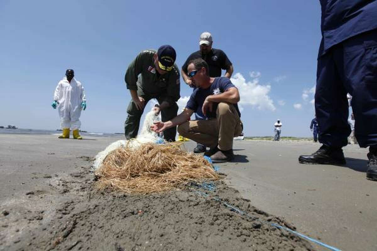 Coast Guard Adm. Thad Allen, National Incident Commander for the Deepwater Horizon oil spill response, center left, looks at absorbent material called snare as he tours oil spill cleanup efforts at Fourchon Beach in Port Fourchon, La., on Thursday, May 27, 2010.
