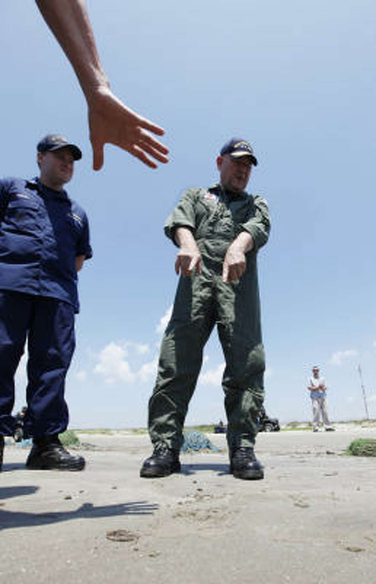 Coast Guard Adm. Thad Allen, National Incident Commander for the Deepwater Horizon disaster response, points at a tar ball as he tours cleanup efforts in Louisiana on Thursday, May 27, 2010.