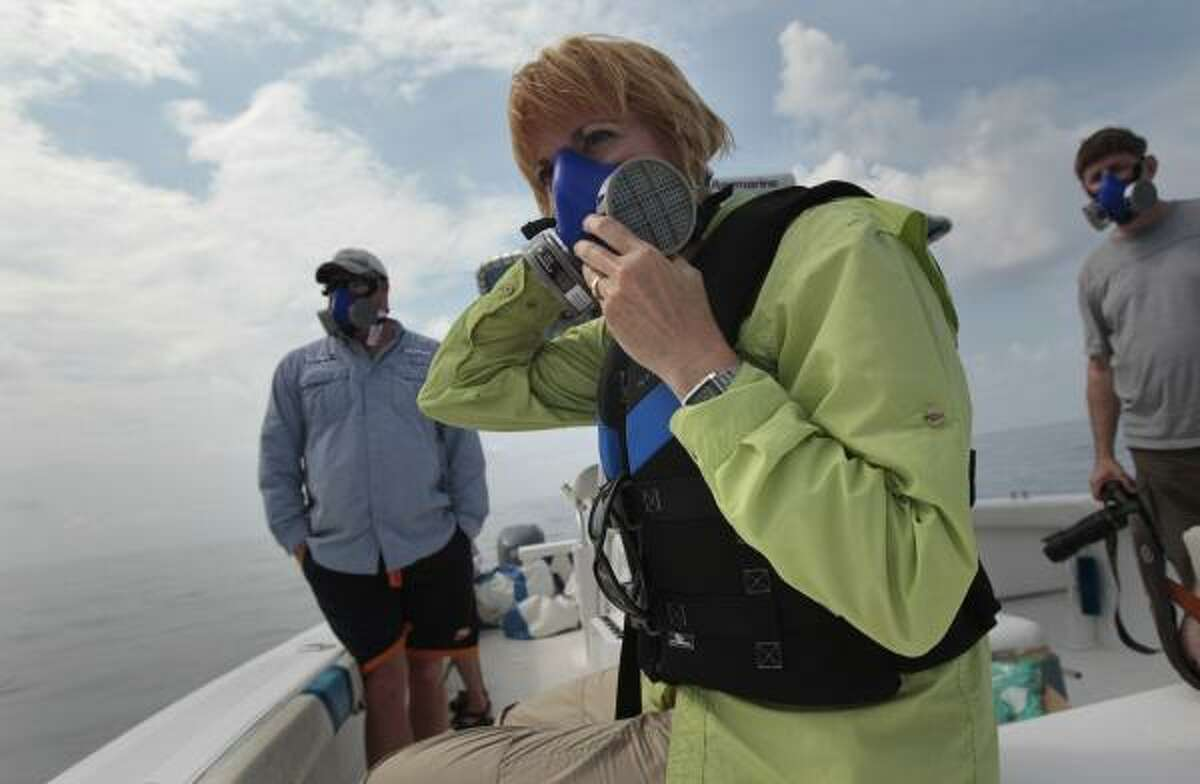National Wildlife Federation program manager Maura Wood, center, wears a mask as she and her colleagues examine oil floating in the Gulf of Mexico near the coast of Louisiana on Wednesday, May 26, 2010.