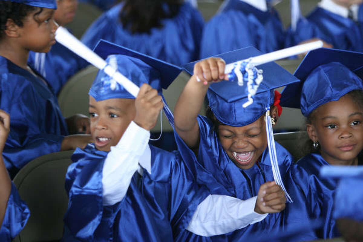 Derrill Foster, 5, and Paige Pobraer, 5, horseplay next to Taylor Brown, 4, after receiving diplomas.