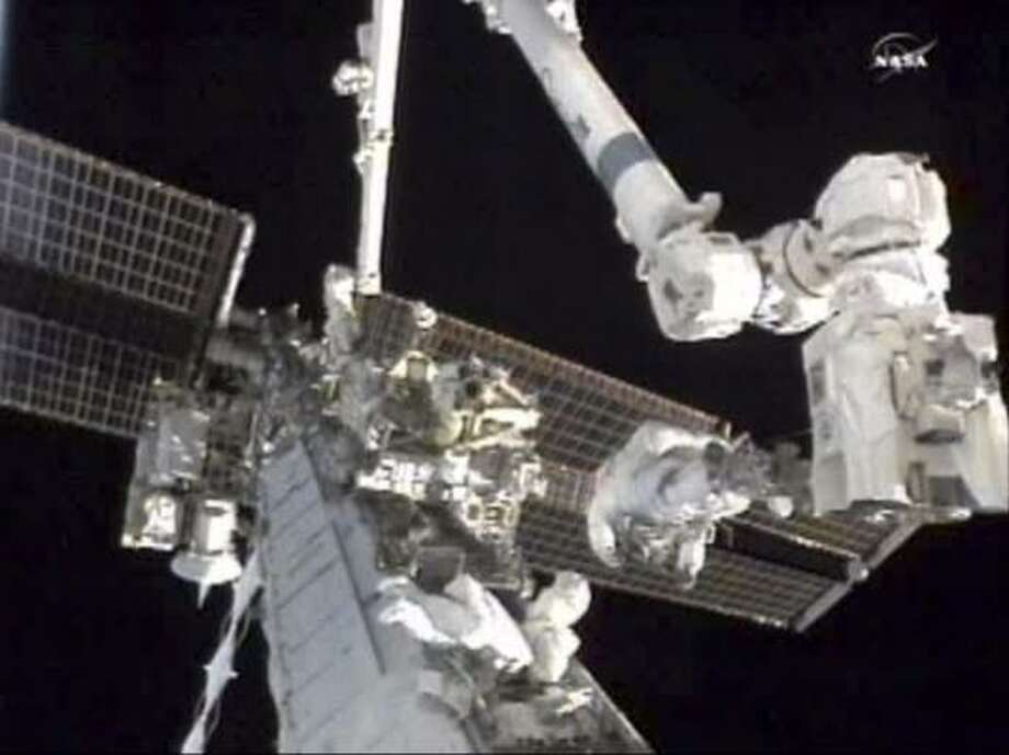 Astronauts Douglas Wheelock, right, and Tracy Caldwell Dyson work to remove a failed cooling pump on the International Space Station on Wednesday. Photo: Associated Press