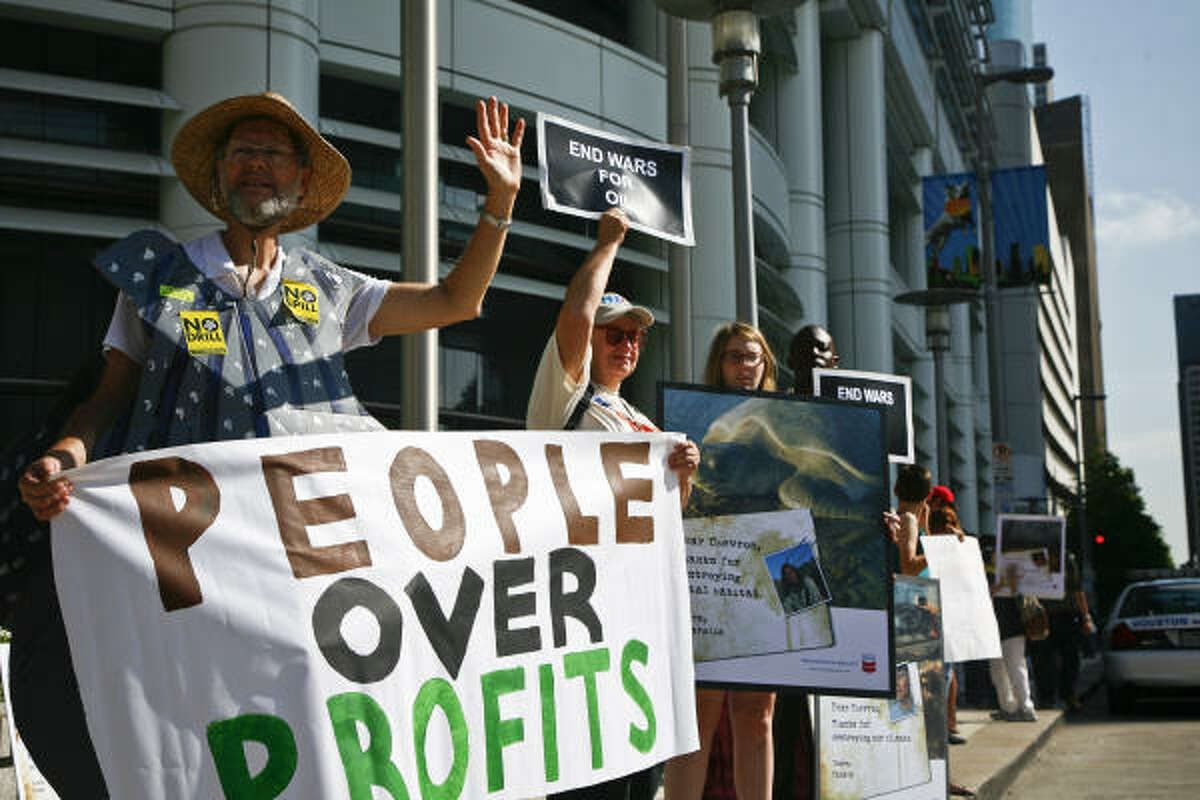 Bill Crosier, left, and his wife, Cheryl, hold up a protest sign along with other activists outside the Chevron building to protest at the company's shareholders meeting Wednesday, May 26, 2010, in Houston.
