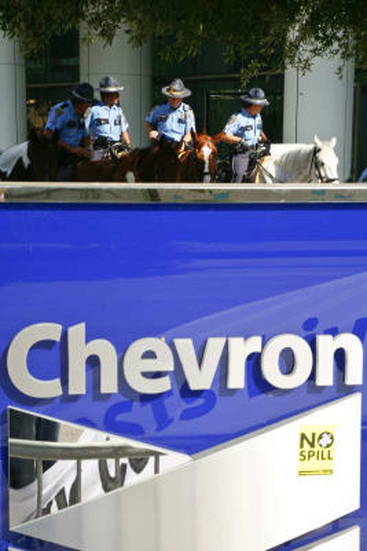 Houston police officers on horses stand guard outside the Chevron building at 1500 Louisiana St. where about 50 activists were on hand to protest the Chevron shareholders meeting Wednesday, May 26, 2010, in Houston.