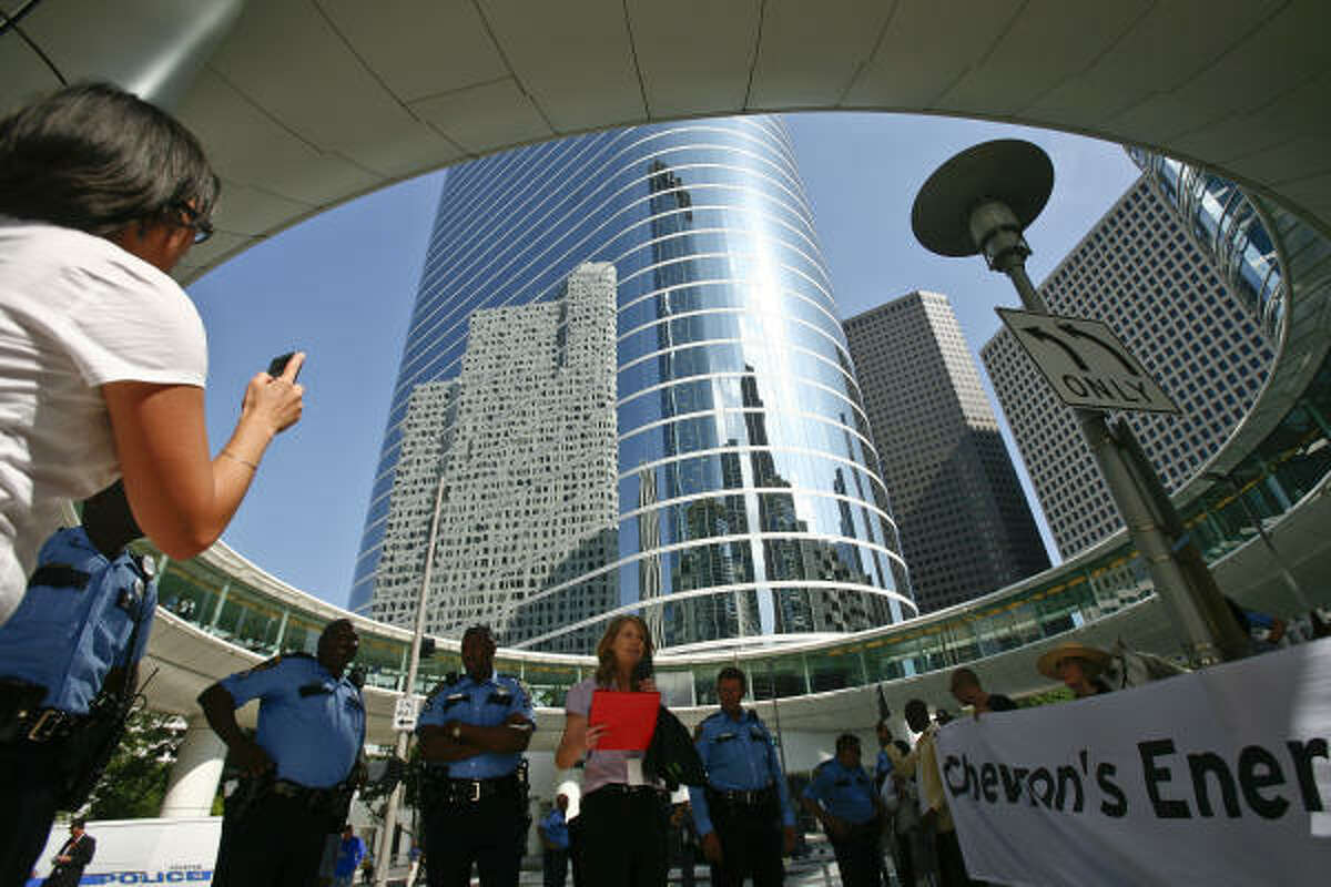 Michelle Kinman, center, rallies protesters outside the Chevron building while the company's shareholders meeting is underway on Wednesday, May 26, 2010, in Houston.