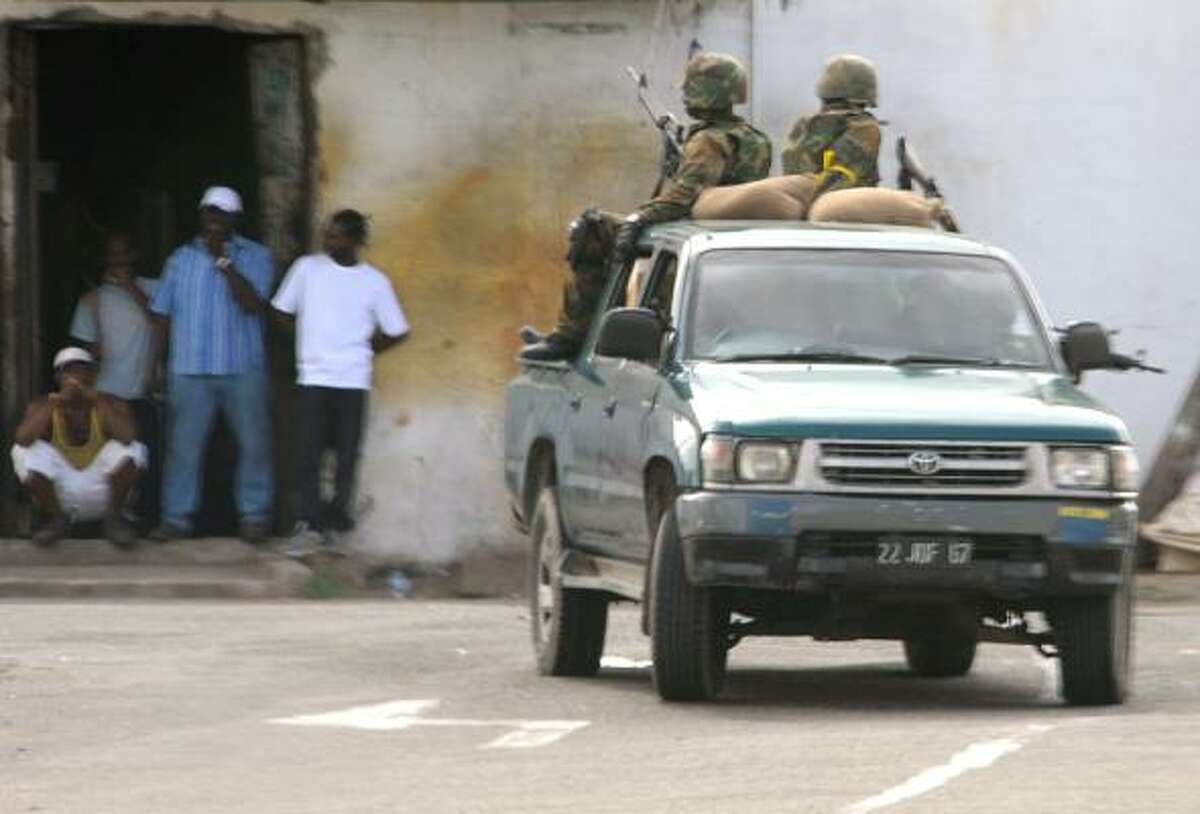 Troops patrol the streets in West Kingston, Jamaica on May 25, 2010. Gun battles raging in the Jamaican capital have left at least 48 people dead, mostly civilians, as troops fanned out across the city hunting alleged drug kingpin Christopher