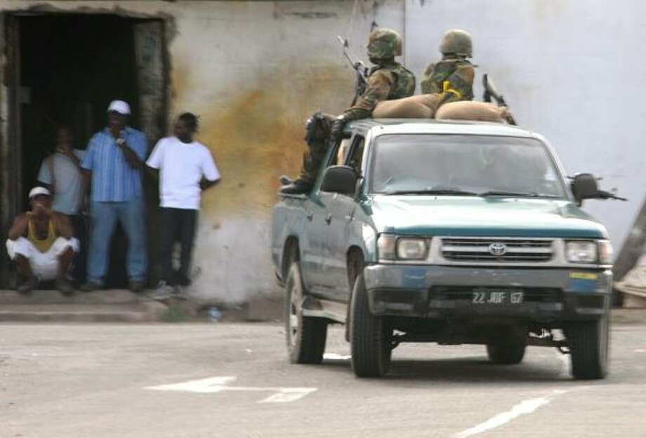 "Troops patrol the streets in West Kingston, Jamaica on May 25, 2010. Gun battles raging in the Jamaican capital have left at least 48 people dead, mostly civilians, as troops fanned out across the city hunting alleged drug kingpin Christopher ""Dudus"" Coke. Hundreds of troops and police have been deployed to hunt down Coke, wanted in the United States on drug-trafficking charges, amid a week-long standoff with his loyal supporters. Photo: AFP/Getty Images"
