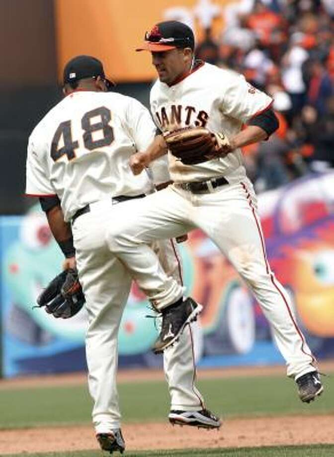 Giants third baseman Pablo Sandoval, left, and left fielder Andres Torres celebrate after the Giants completed the sweep. Photo: George Nikitin, AP
