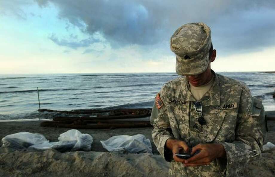 A Louisiana National Guardsman texts while watching over a beach on May 25, 2010, at Elmer's Island, La. The Louisiana coastline is reeling from the effects of the continued gusher. Photo: John Moore, Getty Images