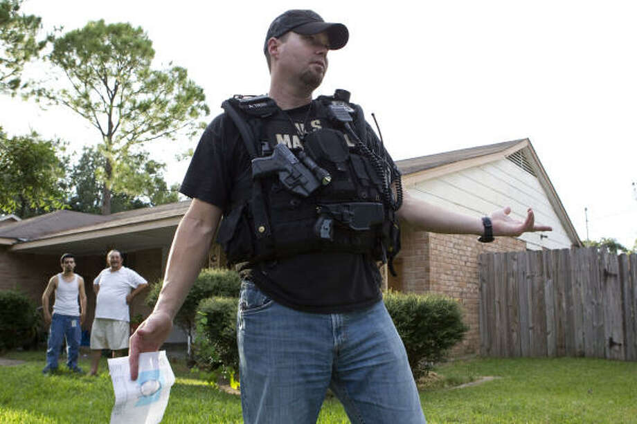 Deputy U.S. Marshal Cameron Welch asks residents for information on a suspect while serving a felony warrant on Aug. 31 in Houston. Photo: James Nielsen, Chronicle