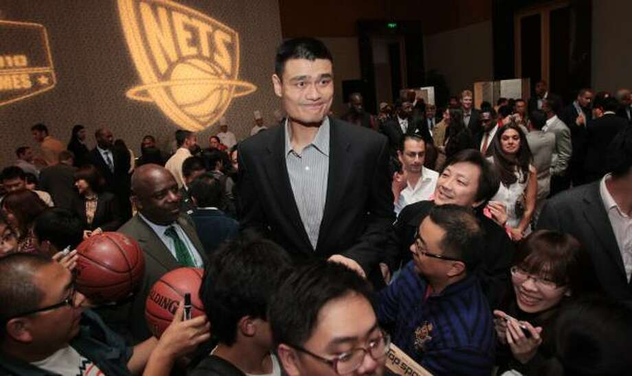 Rockets center Yao Ming expresses some tension as fans push to get his attention at a hotel reception Tuesday marking his return for the China Games in Beijing. Photo: Billy Smith II, Chronicle