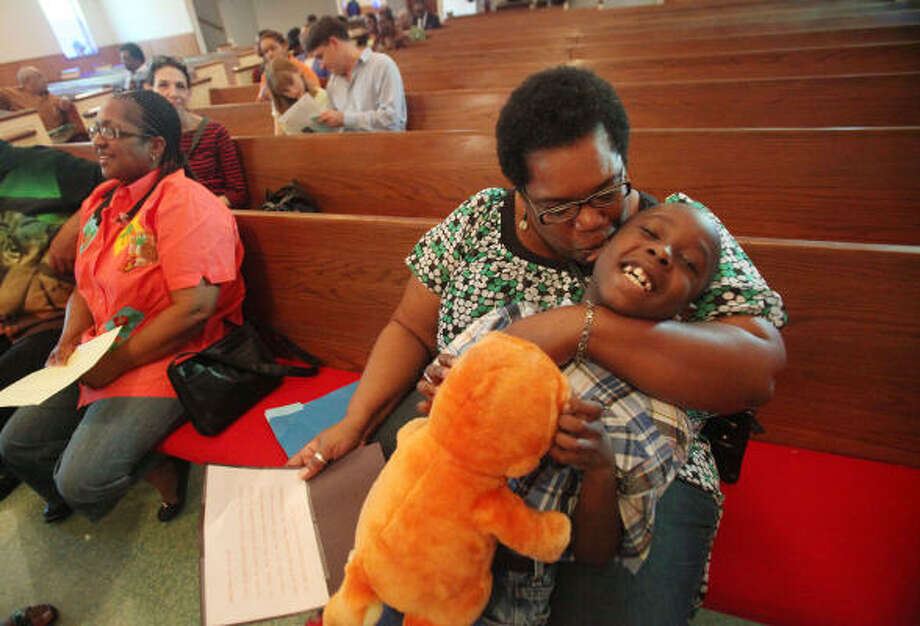 Bronwyn Lucas and her adopted son Jamal, 7, attend a ceremony Sunday at St. Mary's Missionary Baptist Church to highlight the disproportionate number of black children in the Child Protective Services system. Photo: Mayra Beltran, Chronicle