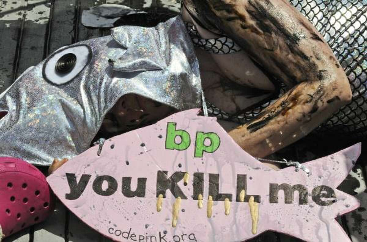 A woman in a fish costume and covered in oil lies on the sidewalk in front of BP headquarters in Houston Monday, May 24, 2010, to stage a protest against the catastrophic Gulf of Mexico oil spill.