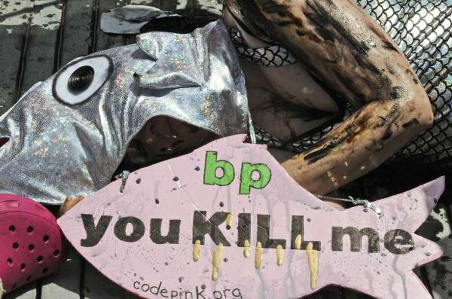 A woman in a fish costume and covered in oil lies on the sidewalk in front of BP headquarters in Houston Monday, May 24, 2010, to stage a protest against the catastrophic Gulf of Mexico oil spill. Photo: Pat Sullivan, AP