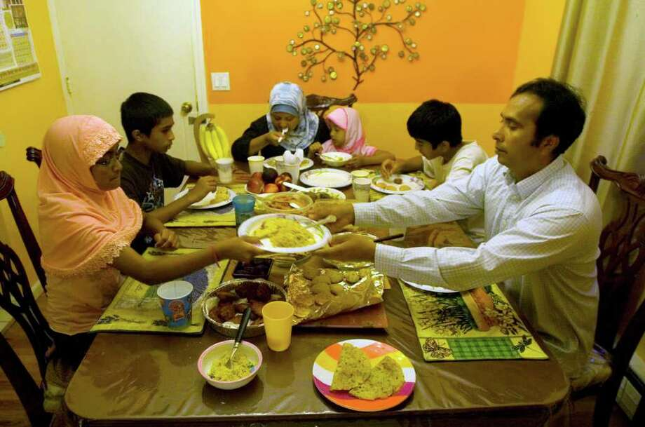The Ahmed family breaks their fast on the third day of Ramadan in Danbury on Wednesday, Aug. 3, 2011.  The Ahmed family from left - Rameezah, 9; Shihab, 11; mother, Shahin; Zainab, 6; and Shahin's brother Muztahid Kaiser, 13, and the Ahmed family patriarch, Rashed. Photo: Jason Rearick / The News-Times