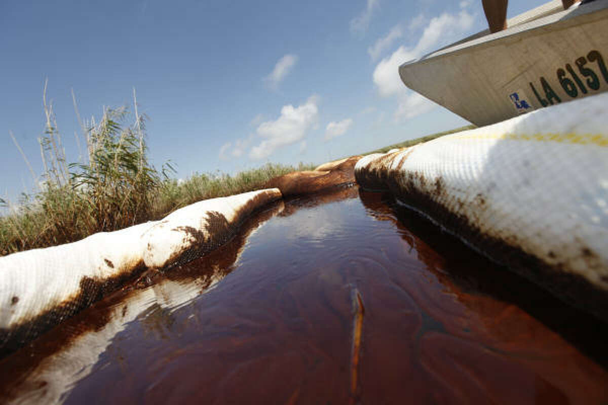 Oil is trapped between two absorbent booms in a marsh in Pass a Loutre, La., that has been affected by the Deepwater Horizon oil spill.