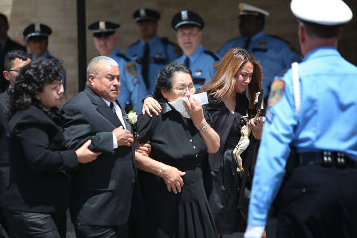 Family members walk to the funeral mass for Houston Police Officer Eydelmen Mani at St. Charles Borromeo Catholic Church. Officer Mani was born in Mexico City, and joined the Houston Police Department in 2003. Mani died of injuries after crashing his squad car into a guardrail on a north Houston freeway while rushing to join fellow officers chasing a suspected car thief earlier this week.