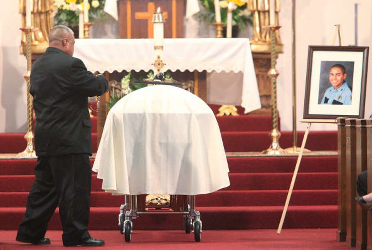 A family member places a rosary on the casket of Houston Police Officer Eydelmen Mani.