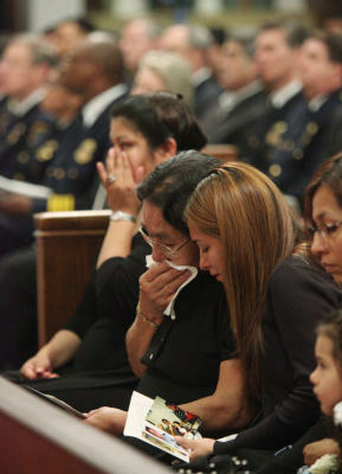 Family members weep during the funeral mass for Houston Police Officer Eydelmen Mani at St. Charles Borromeo Catholic Church.