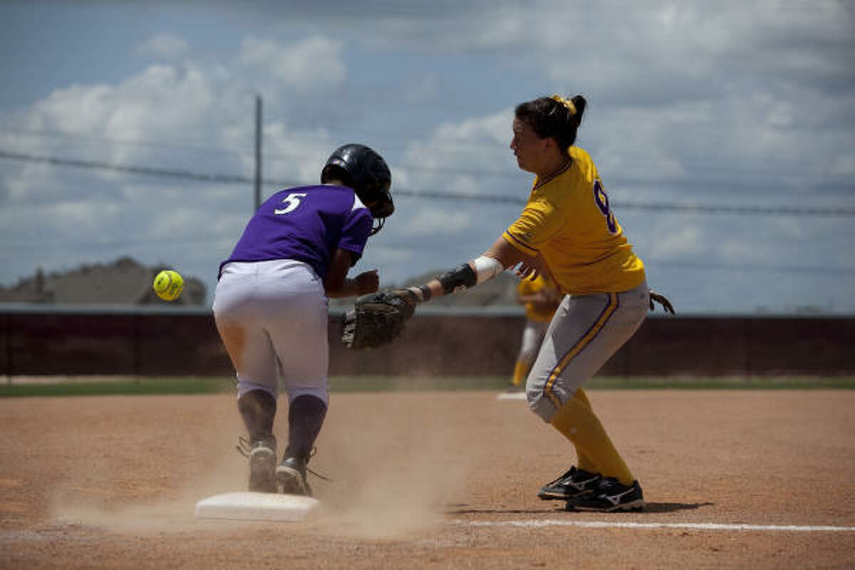 Angleton's Tiffany Robertson gets a ball in the elbow after sliding into third base in front of Montgomery third baseman Peyton Webb in the top of the fifth inning.