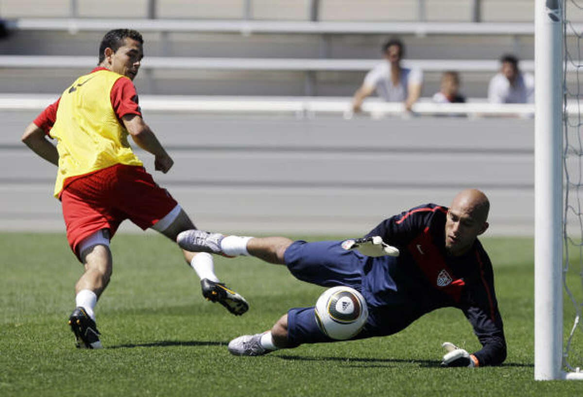Herculez Gomez, left, looks on as goalkeeper Tim Howard dives for the ball at the U.S. camp in Princeton, N.J.