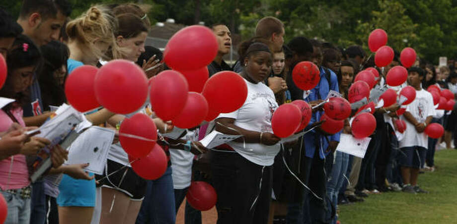 Bellaire High School students are seen on the track of the school with red balloons they released in remembrance of fellow student Tobi Oyedeji's birthda in Houston. Oyedeji died in a car accident on his way home from Prom. Photo: Julio Cortez, Chronicle