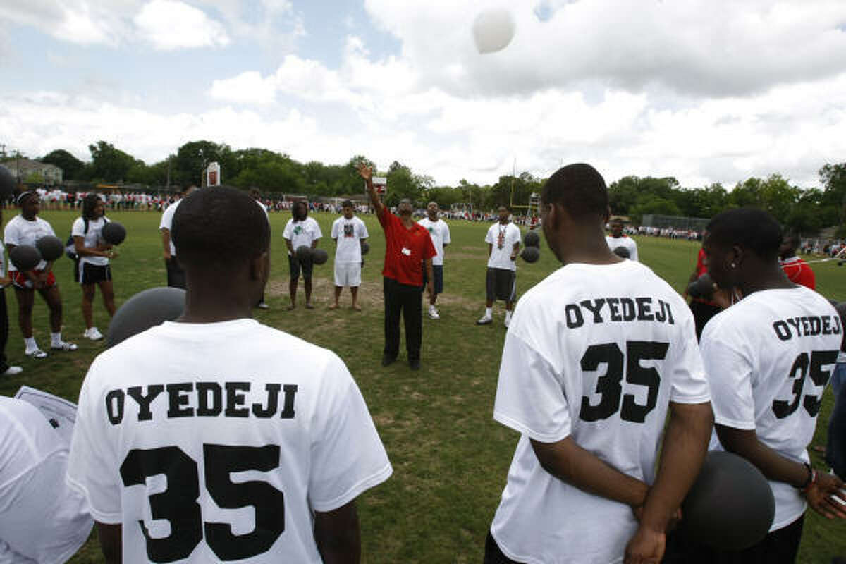 Bellaire High School boys' basketball coach Bruce Grover, center, releases a white balloon as he and members of the team gathered in remembrance of fellow student Tobi Oyedeji's birthday.