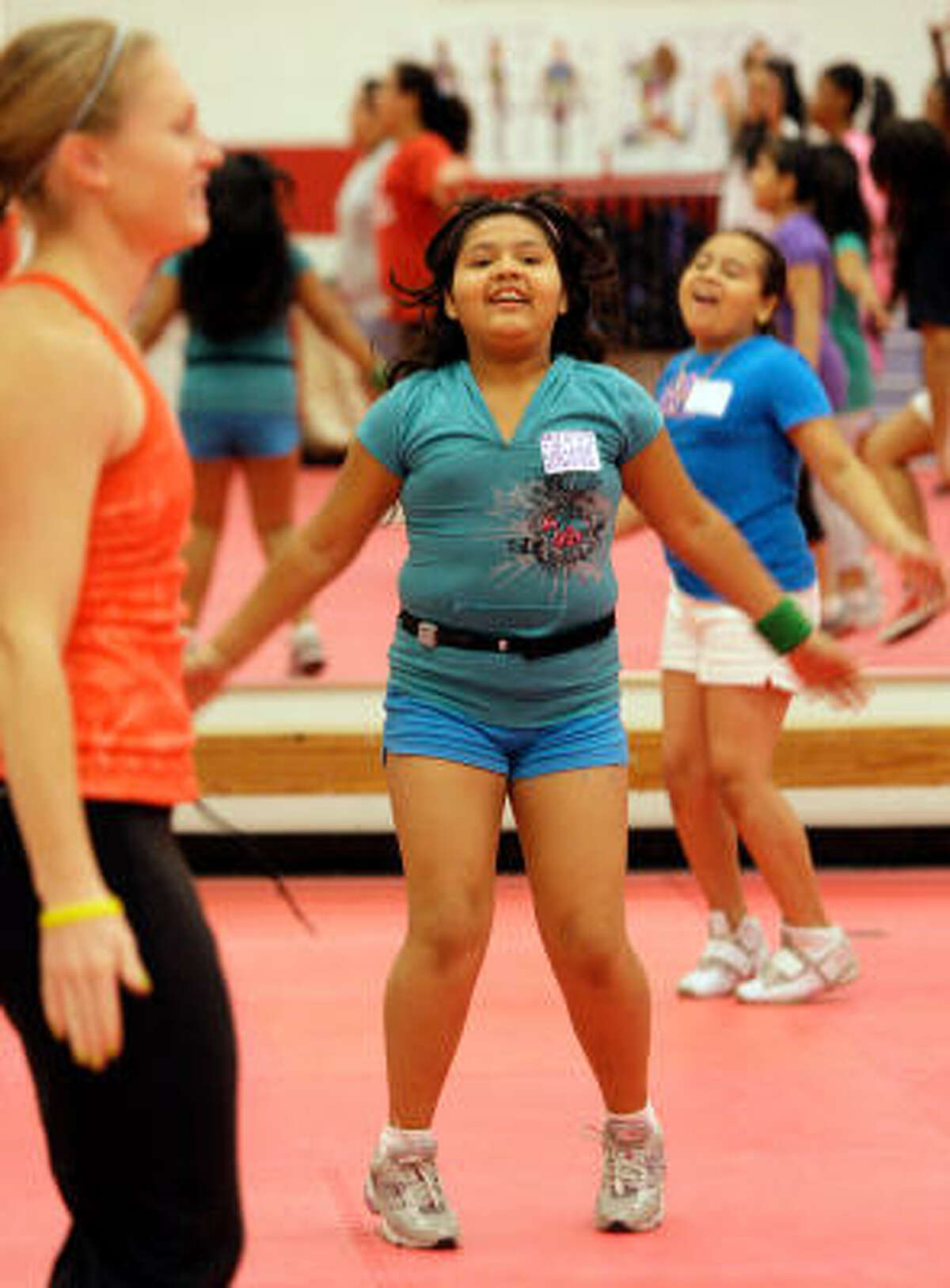 Emily Gonzalez, center, and Joanna Yanes, right, take part in a yoga class at the Behavior Opportunities Uniting Nutrition Counseling and Exercise, a summer program for girls at the University of Houston.