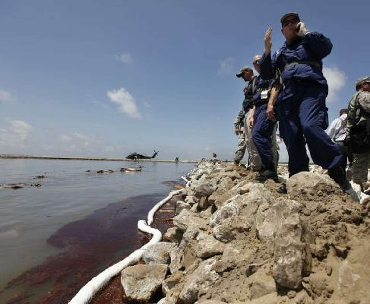 U.S. Coast Guard and Louisiana National Guard personnel look at encroaching oil from a land bridge in Grand Isle, La., built by the National Guard to lessen damage from the Deepwater Horizon disaster.