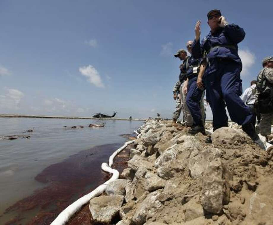 U.S. Coast Guard and Louisiana National Guard personnel look at encroaching oil from a land bridge in Grand Isle, La., built by the National Guard to lessen damage from the Deepwater Horizon disaster. Photo: Gerald Herbert, AP
