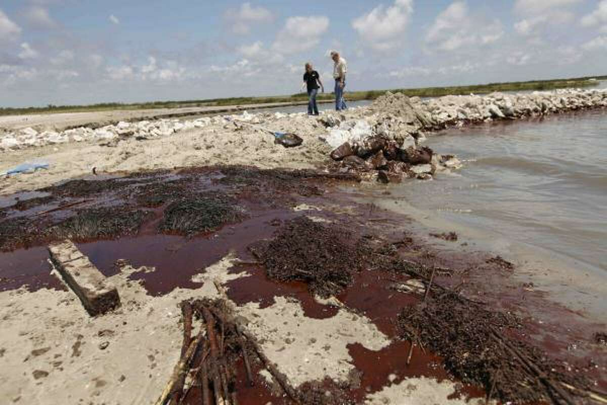 Oil washes ashore against a land bridge in Grand Isle, La.
