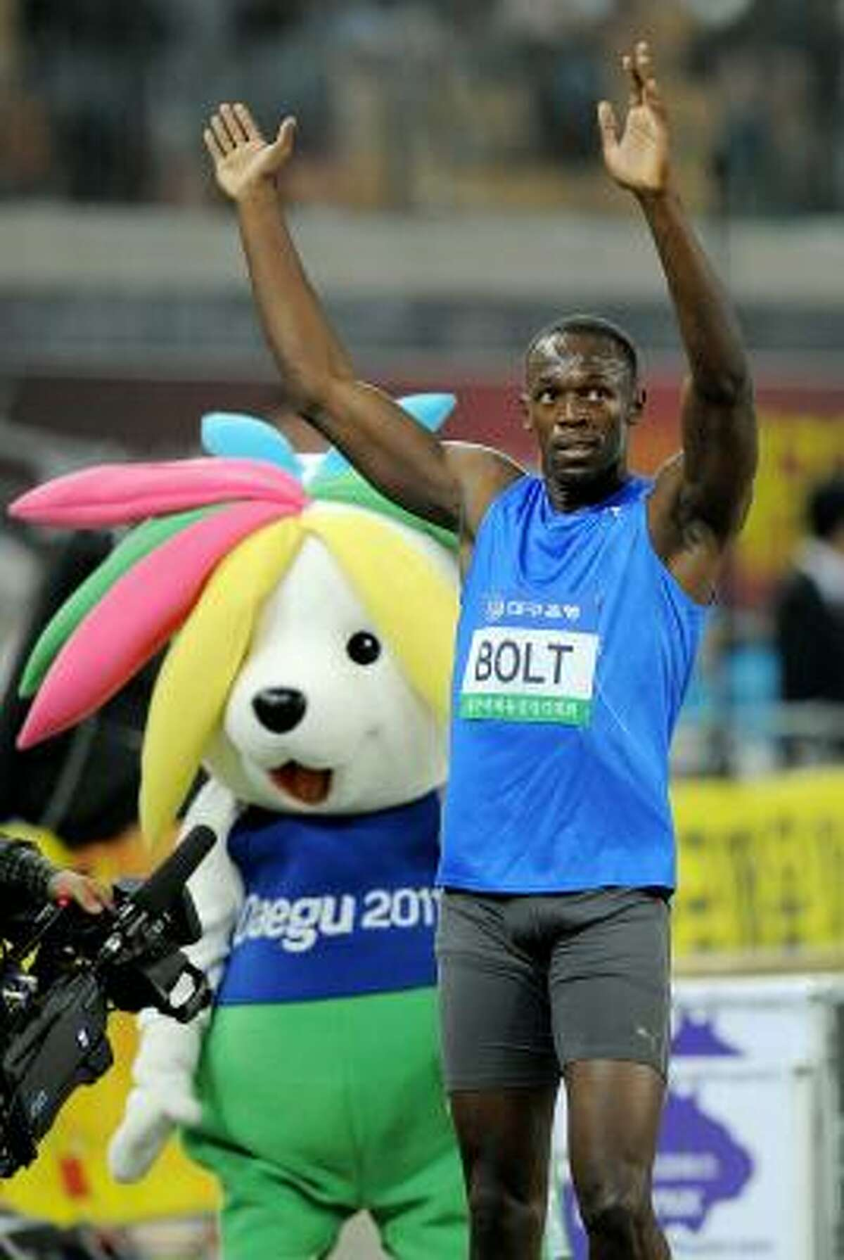 2010 DAEGU PRE-CHAMPIONSHIPS While Usain Bolt celebrates another 100-meters win at this track and field meet in Daegu, southeast of Seoul, Korea on May 19, the event's Sansabelt-golf-pants-wearing, gigantic-flower-in-its-hair mascot ruins the shot.