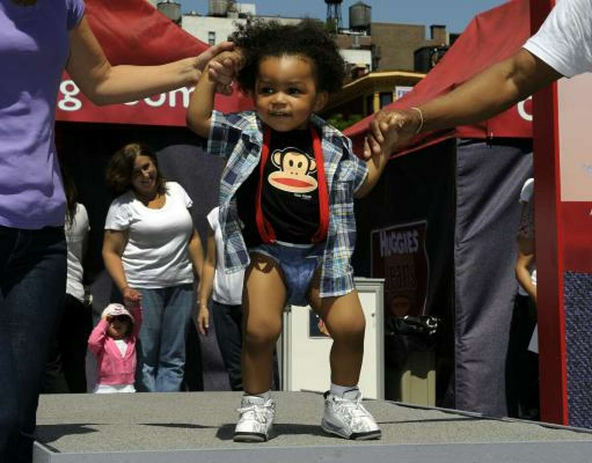 A toddler shows off his new Huggies Little Movers Jeans Diapers during a baby fashion show in New York City.