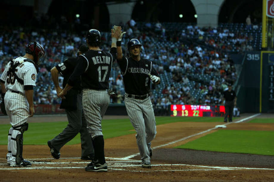 May 20: Rockies 4, Astros 0Rockies' Troy Tulowitzki, right, is greeted by teammate Todd Helton at home plate after Troy Tulowitzki hit a three run home run off Roy Oswalt in the first inning. Photo: Johnny Hanson, Chronicle
