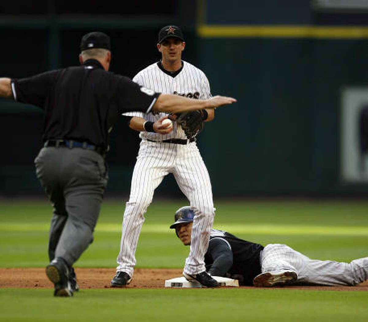 Rockies' Carlos Gonzalez is called safe next to the Astros' Tommy Manzella by second base umpire Ted Barrett after Gonzales stole the base in the first inning.