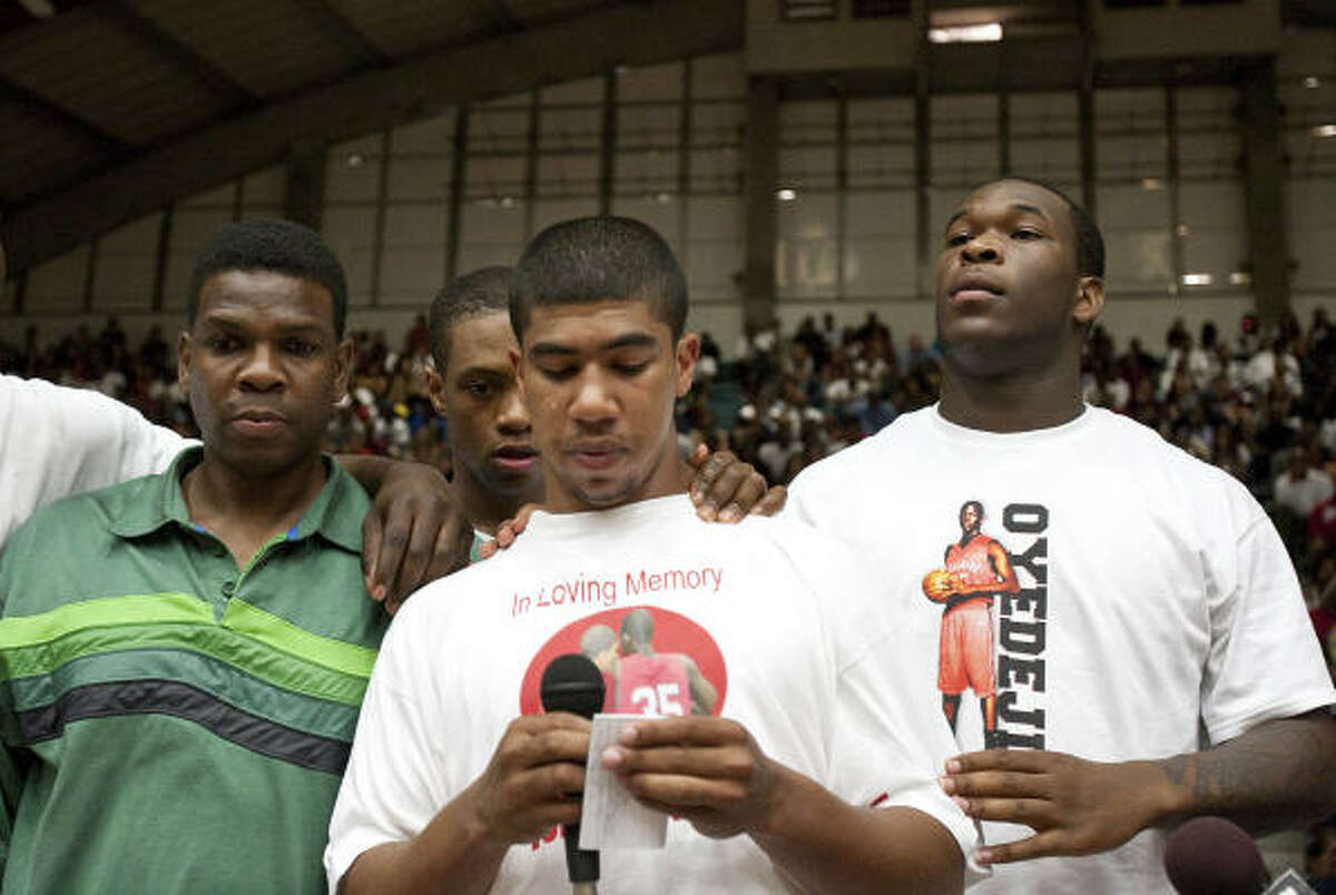 Jonathan Evans, center, sheds a tear as he makes a statement for a charity basketball game in memory of his friend Tobi Oyedeji.